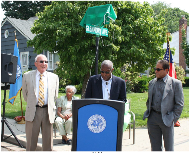 (L-R) Village of Hempstead Mayor Wayne J. Hall Sr. (center) welcomes the Theta Iota Omega Chapter, congratulating them on their dedication to helping Village residents access opportunities while Village of Hempstead Trustee Don Ryan and Deputy Mayor Luis Figueroa look on. The Village recently dedicated Saint Regis Place to Alpha Kappa Alpha Sorority, Incorporated, Theta Iota Omega Chapter in honor of the organization's 50 years of service and to local community leader Dr. Terrecita Watkis.