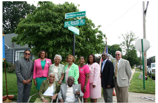 Village of Hempstead Deputy Mayor Luis Figueroa; Kiona P. DeWitt, Theta Iota Omega Chapter President; Dr. Marion Fleming, Charter Member; Doris White, Charter Member; Wilma Holmes Tootle, Alpha Kappa Alpha Sorority, Inc. International Sisterly Relations Chairman; Leah E. Watson, Theta Iota Omega Chapter, 50th Anniversary Chairman; Village of Hempstead Mayor Wayne J. Hall Sr. and Village of Hempstead Trustee Don Ryan stand to honor local community leader and Charter member Dr. Terrecita Watkis (seated) and Mr. Roy Watkis (seated). The Village recently dedicated Saint Regis Place to Alpha Kappa Alpha Sorority, Incorporated, Theta Iota Omega Chapter in honor of the organization's 50 years of service.
